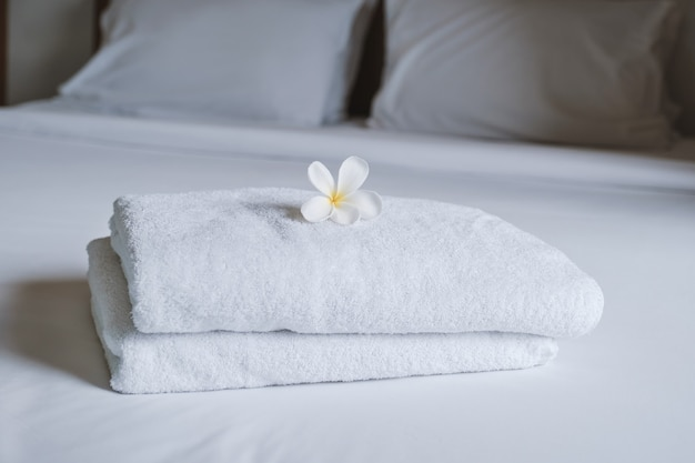 Plumeria en handdoeken op het bed in de luxe hotelkamer klaar voor toeristische reizen.