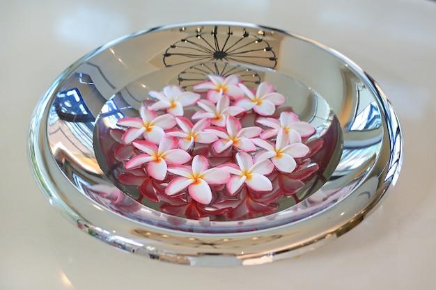 Plumeria of frangipani-bloem die in water in aluminiumdienblad drijft. kuuroordconcept bloeiende bloemen.
