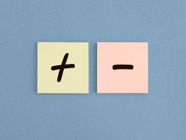 Plus- en mintekens op papier. concept van positief en negatief, voor- en nadelen. goede vs slechte vergelijking.