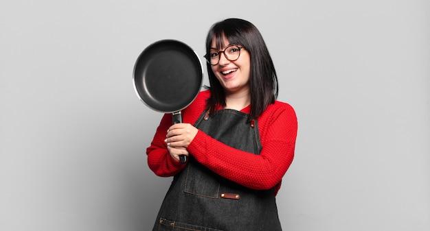 Plus grootte mooie chef-kok vrouw koken met een pan