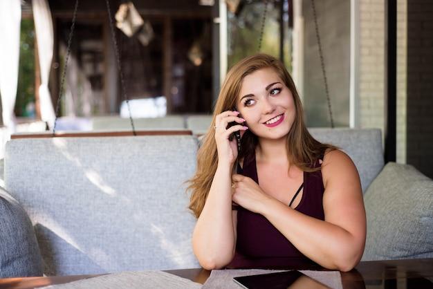 Plus grootte mooie jonge vrouw met tablet en telefoon in een restaurant.