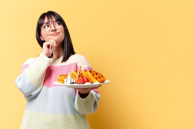 Plus grootte mooie vrouw die wafels eet