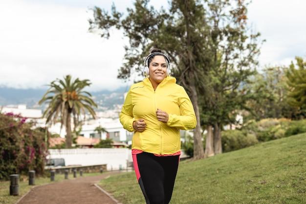 Plus grootte vrouw joggen buiten in stadspark - belangrijkste focus op koptelefoon