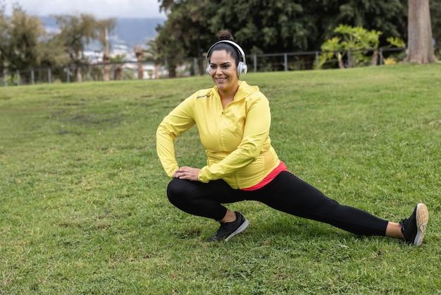 Plus size meisje doet stretching dagroutine buiten in het stadspark - focus on face