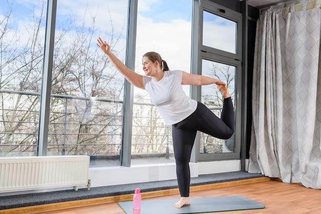 Plus-size meisje oefent binnen trainen, sta op een been naar beneden en steek de hand omhoog met ok gebaar