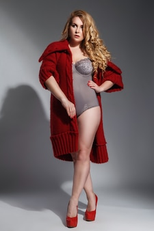 Plus-size model draagt lingerie en rode gebreide jas