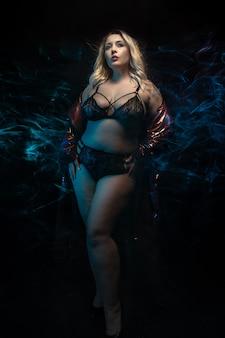 Plus-size model in zwarte lingerie.