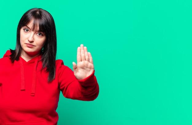 Plus-size mooie vrouw die er serieus, streng, ontevreden en boos uitziet en open handpalm laat zien en stopgebaar maakt