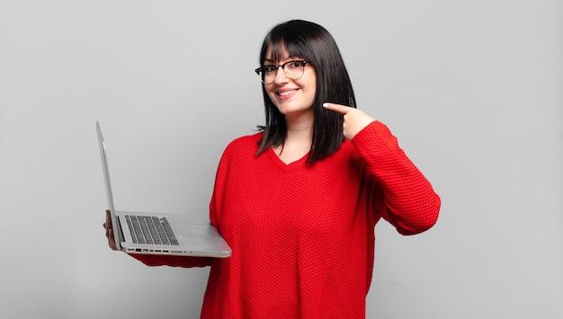 Plus size mooie vrouw glimlachend vol vertrouwen wijzend naar eigen brede glimlach, positieve, ontspannen, tevreden houding