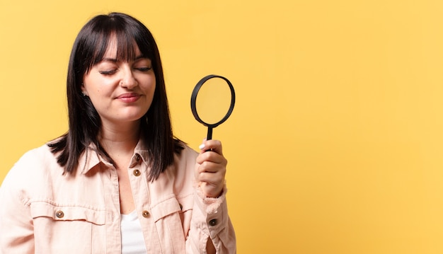 Plus size mooie vrouw kijkt met een vergrootglas