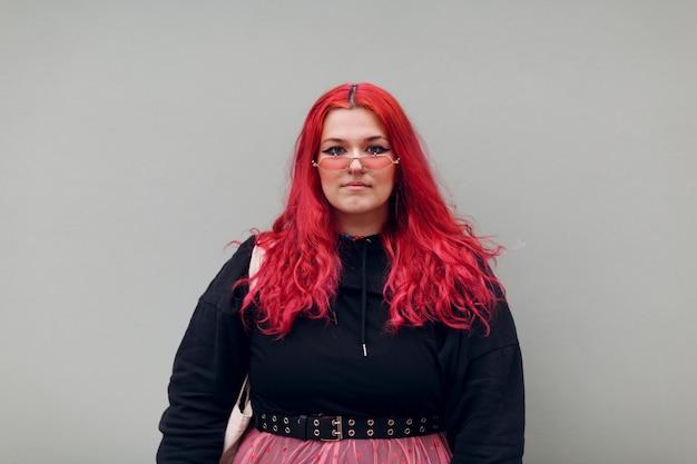 Plus size overgewicht vet vet lichaam positieve lgbtq vrouw met rood haar en roze bril.
