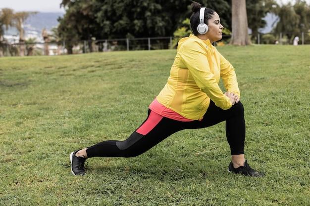 Plus size vrouw doet sport workout routine buiten in stadspark