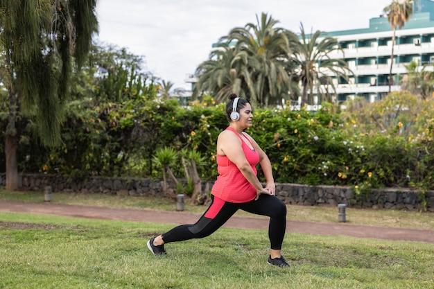 Plus size vrouw doet stretching dagroutine buiten in het stadspark - focus on face