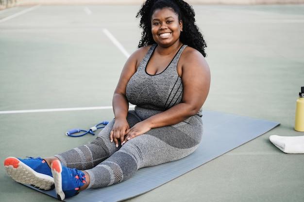 Plus size vrouw doet workout routine buiten bij stadspark - focus op gezicht