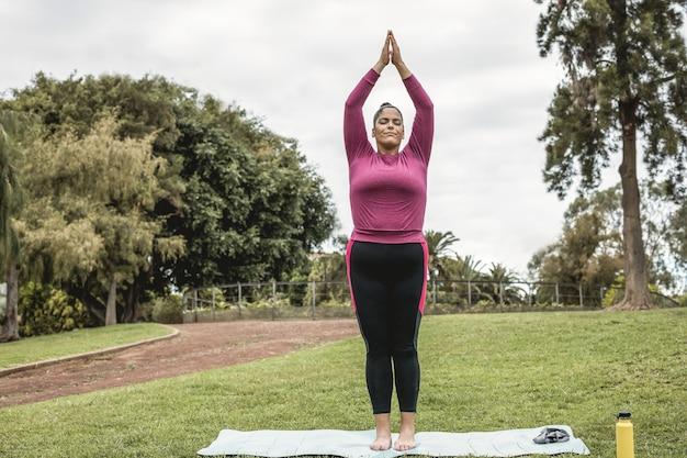 Plus size vrouw doet yoga-sessie buiten in het stadspark - focus op gezicht