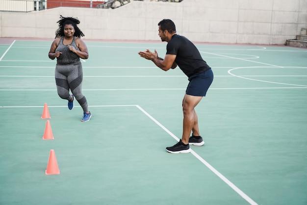 Plus size vrouw en personal trainer doen snelheid en behendigheid kegeloefeningen trainingssessie buiten