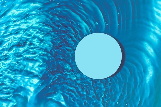 Podium bovenaanzicht onder transparante watergolven op blauwe achtergrond voor product- en cosmetische presentatie. minimaal water achtergrondconcept