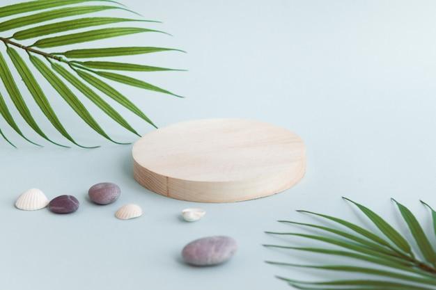 Podium voor cosmetische of gezondheidsproducten cirkelscène met palmbladeren en kiezelstenen op blauwe b