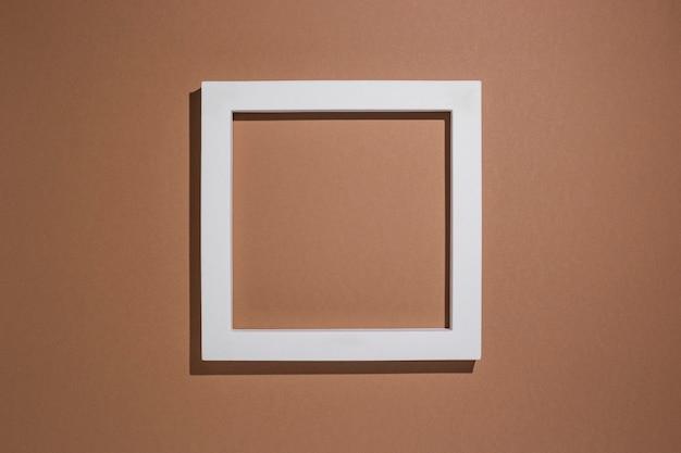 Podium voor presentatie vierkant wit frame op bruine achtergrond. bovenaanzicht, plat gelegd.