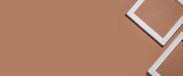 Podium voor presentatie vierkante witte frames op bruine achtergrond. bovenaanzicht, plat gelegd. banier.