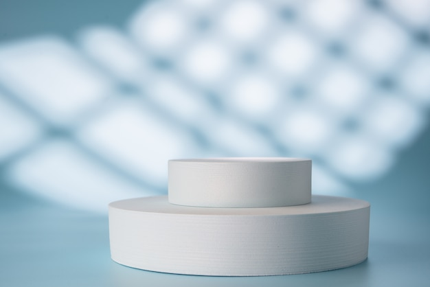 Podium voor productpresentatie op blauwe achtergrond met schaduwen en licht