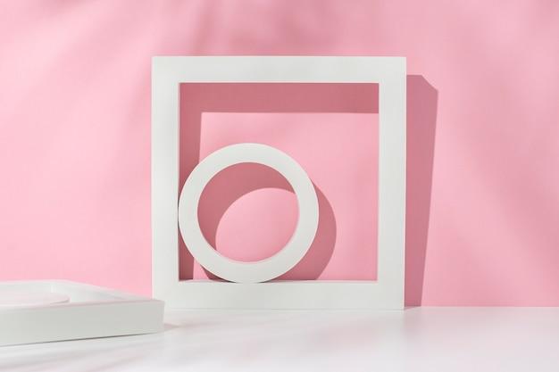 Podium wit vierkant, cirkels voor presentatie onder de schaduw van palmbladeren op een wit roze