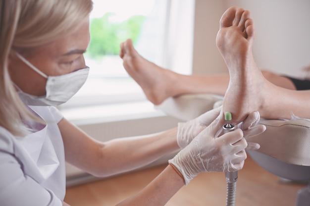 Podoloog die gebruik maakt van slijpapparatuur en polijstprocedures maakt voor voetpedicure