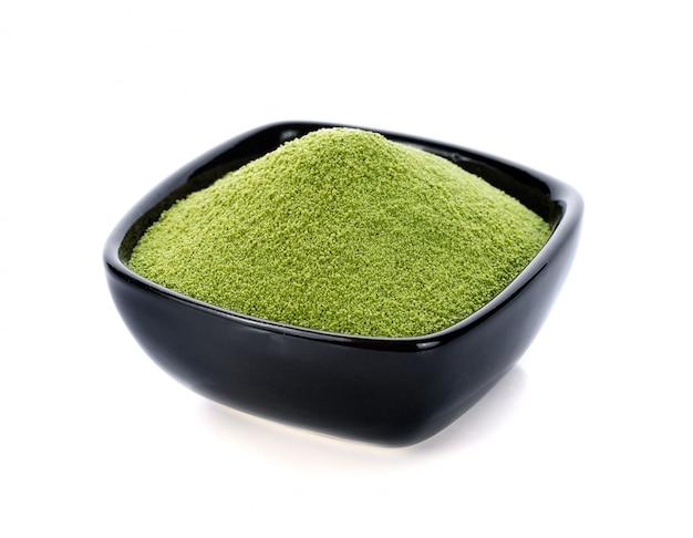 Poeder groene thee die op wit wordt geïsoleerd