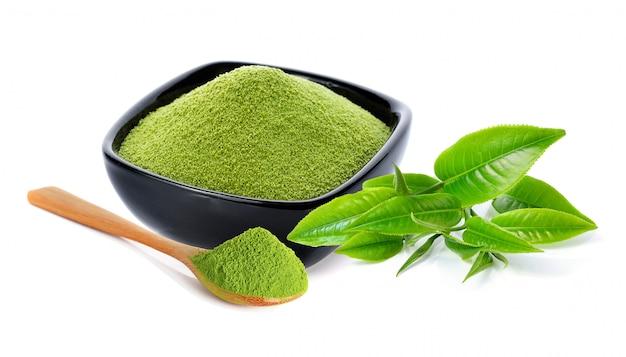 Poeder groene thee en groen theeblad op wit wordt geïsoleerd dat