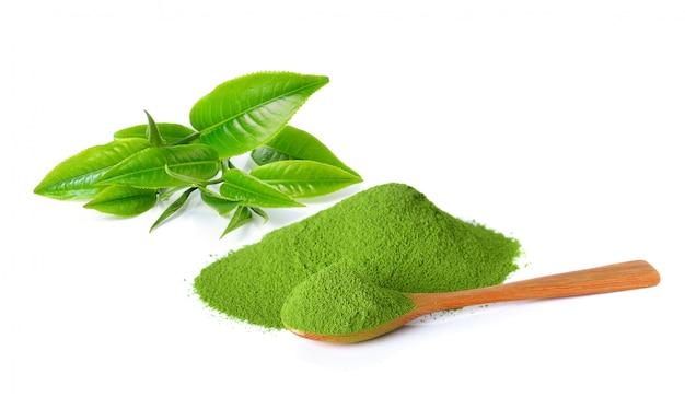 Poeder groene thee en groen theeblad op witte achtergrond wordt geïsoleerd die