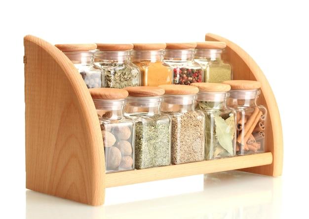 Poeder kruiden in glazen potten op houten plank geïsoleerd op wit