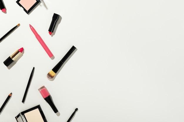 Poeder, markeerstift, lippenstift, make-upborstels en nagellak op wit wordt geïsoleerd