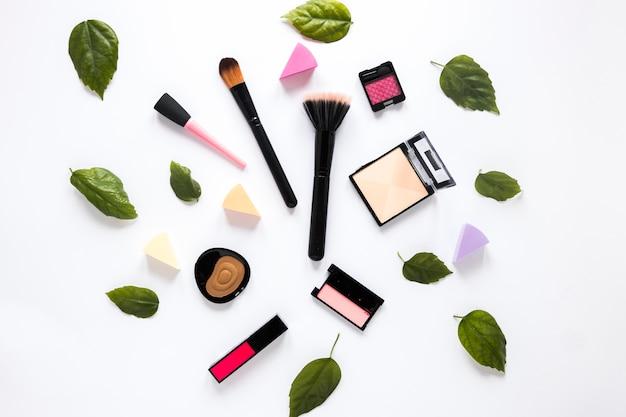 Poederborstels met cosmetica en groene bladeren