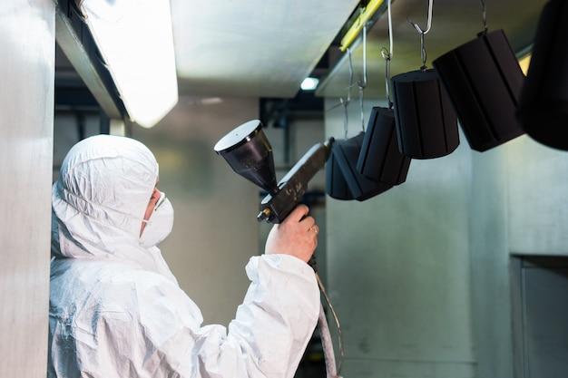 Poedercoating van metalen onderdelen. een man in een beschermend pak spuit poederverf van een pistool op metalen producten