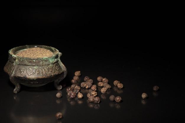 Poedervormige zwarte peper en peperkorrels op zwarte ondergrond