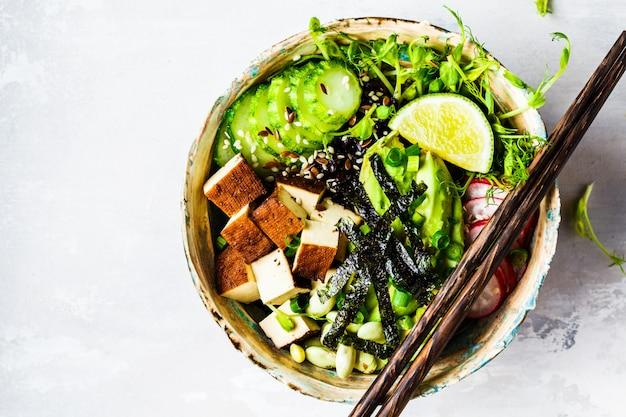Poke bowl met avocado, zwarte rijst, gerookte tofu, bonen, groenten, spruitjes