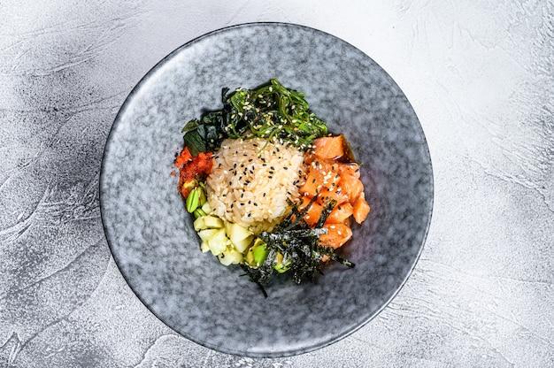 Poke bowl met rauwe zalm, rijst en groenten. grijze achtergrond. bovenaanzicht