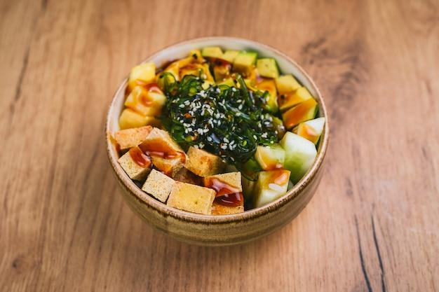 Poke bowl met tofu, komkommer, avokado, mango en chuka salade