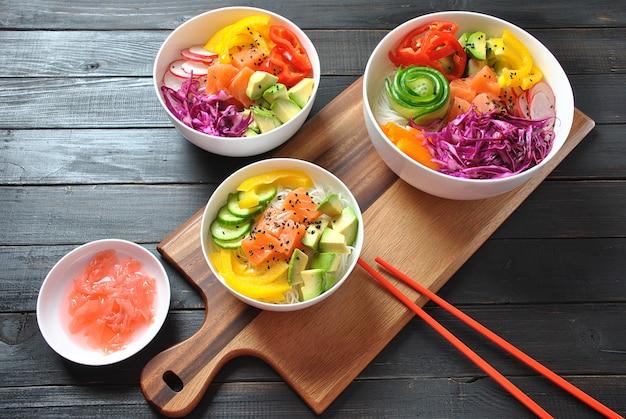 Poke bowls met verse zalm, crystal noodles, radijs, avocado, paprika, komkommer, sesamzaadjes, rode kool. biologisch voedsel. recept voor verse zeevruchten. het voedselconcept port kom op houten achtergrond
