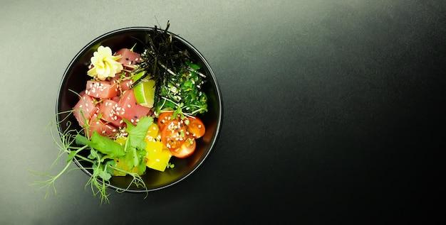 Poke salade met tonijn in een kom. ingrediënten verse tonijn, cherrytomaatjes, gemarineerd zeewier, rijst, takuan, ponzu-saus, teriyakisaus, nori, sesamzaadjes, limoen, koriander. aziatische zeevruchten salade concept.