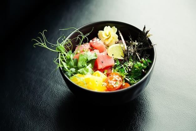 Poke salade met tonijn in een kom ingrediënten verse tonijn cherrytomaatjes gemarineerd zeewier