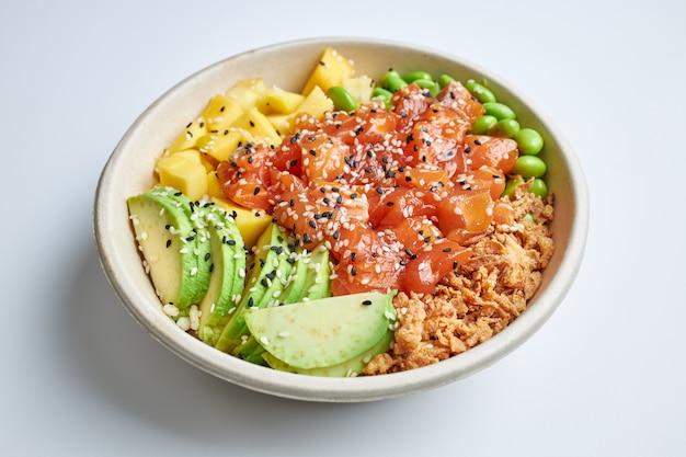 Poke salade met zalm, avocado, mango, edamame, krokante ui en sesamzaadjes.