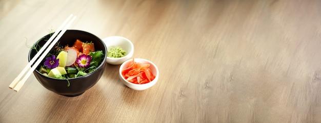 Poke salade met zalm in een kom naast wasabi en gember. ingrediënten verse zalm, avocado, komkommer, rijst, tamarindesaus, mangosaus, nori limoen sesamzaadjes koriander. aziatische zeevruchten salade concept