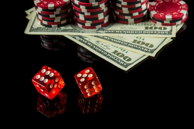 Poker dobbelstenen met winnende combinatie van elf op zwarte tafel en chips met dolars op de achtergrond