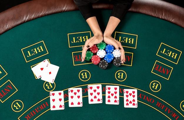 Poker spelen. chips in de hand van een speler. bovenaanzicht. de speler zet all-in in. vrouwenhanden zijn bewegende fiches