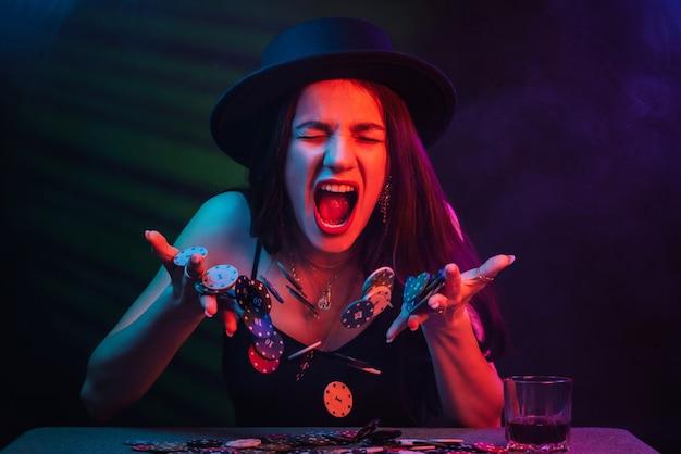 Poker spelen en gokken in casino. emotioneel meisje geeft chips over. concept van geluk, winnen en verliezen