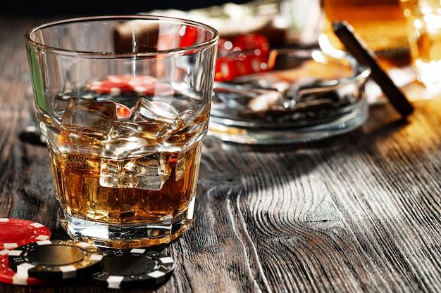 Poker spelen met whisky en sigaren op tafel