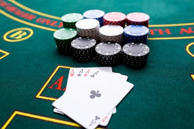 Pokerfiches op een pokertafel in het casino. detailopname. vier azen, een winnende combinatie. chips winnaar