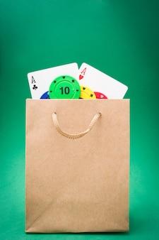 Pokerkaarten en pokerfiches in zak op groene achtergrond