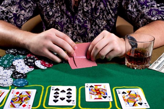 Pokerkaarten in de hand op een pokertafel